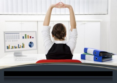 Lady sitting at work desk with arms stretched in the air.
