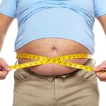 Fat, overweight man with tape measure around his belly