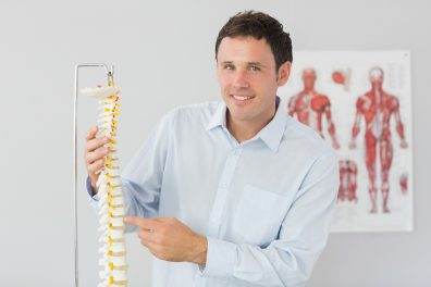 Osteopath trainer pointing at model of a spine
