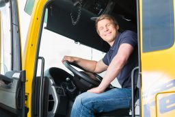 Logistics - proud driver or forwarder in drivers cap of truck an