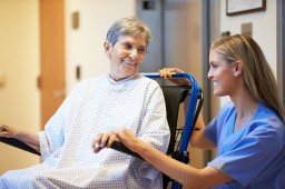 Senior Female Patient Being Pushed In Wheelchair By Nurse