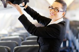 Lady using Manual Handling to stow overhead luggage on a plane